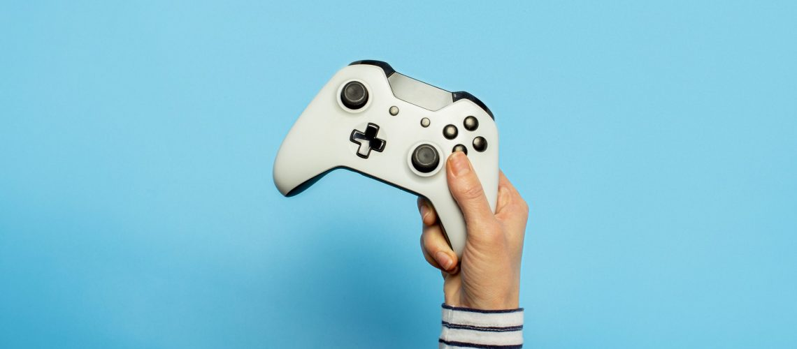 Female hand hold a gamepad on a blue background. Concept of the game, e-sports, leisure, gaming industry, video games. Banner. Flat lay, top view.